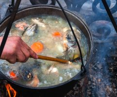 cooking fish soup in a pot on the fireplace